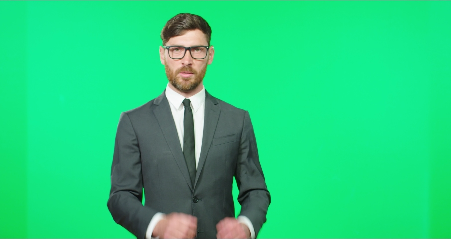 Successful TV presenter in glasses with beard in suit tells news live looking into camera gesturing with his hand. Royalty-Free Stock Footage #1069180444