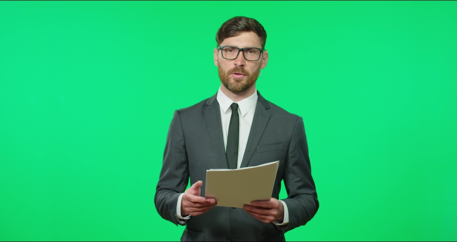Young Caucasian TV presenter in glasses and suit reading news holding paper with text. Business news on television. Royalty-Free Stock Footage #1069180498