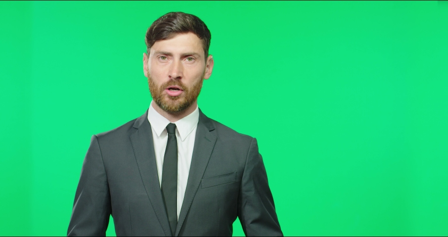 Caucasian presenter in business suit with tie tells news block sitting in studio on green screen background. Royalty-Free Stock Footage #1069180552