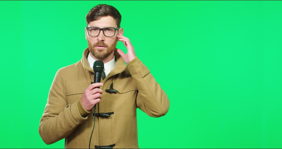 Young Caucasian male journalist with glasses and coat gets in touch with news studio and conducts report holding microphone. Royalty-Free Stock Footage #1069180591