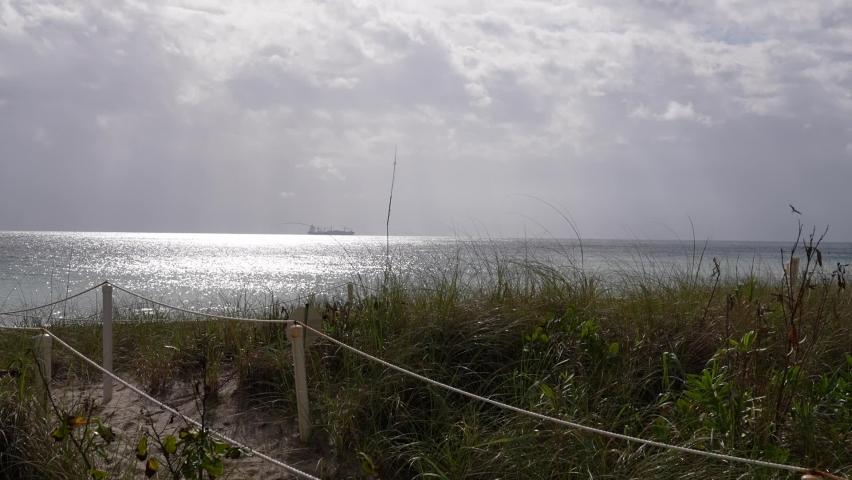 Sun shining through partly cloudy sky down on the Atlantic ocean in Fort Lauderdale, Florida. Barge anchored in the distance. Beautiful beach day. | Shutterstock HD Video #1069181308