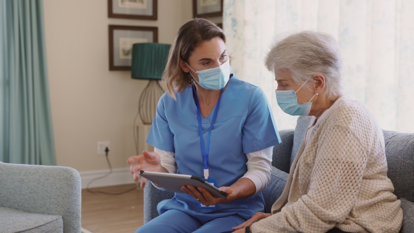 Young nurse and senior woman going through medical record on digital tablet during home visit and wearing face mask. Doctor during covid pandemic showing medical reports to old woman at nursing home.  | Shutterstock HD Video #1069200016