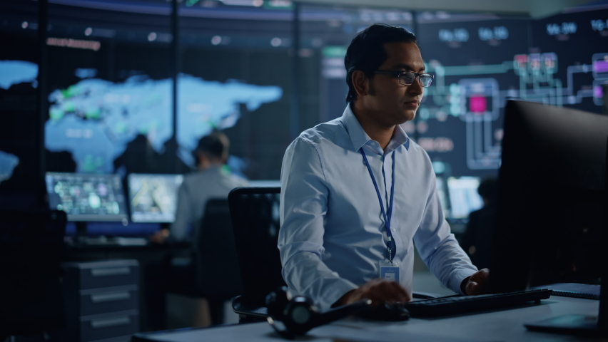 Professional IT Technical Support Specialist and Software Developer Working on Computer in Monitoring Control Room with Digital Screens with Server Data, Blockchain Network and Surveillance Maps. Royalty-Free Stock Footage #1069211362