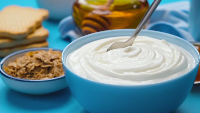 Bowl of sour cream on blue background, greek yogurt Royalty-Free Stock Footage #1069213711