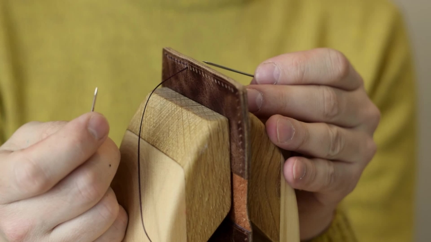 The process of manufacturing a leather cardholder.Artisan sewes the details of a cardholder fixed in a wooden saddler.Handmade leather goods.Hobby concept.Hands close-up, slow motion. Royalty-Free Stock Footage #1069243654