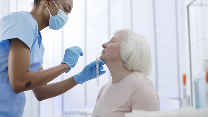 Young female medical nurse in protective mask and gloves taking PCR test sample from nose of pensioner patient and put it into glass tube . Concept of Covid diagnostic. Royalty-Free Stock Footage #1069256587