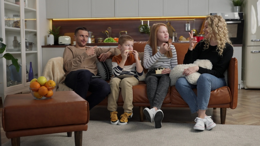 Cheerful parents and their kids with hearing disability communicating using sign language sitting on couch, girl and boy eating sandwiches. People with hearing loss relaxing on sofa watching TV