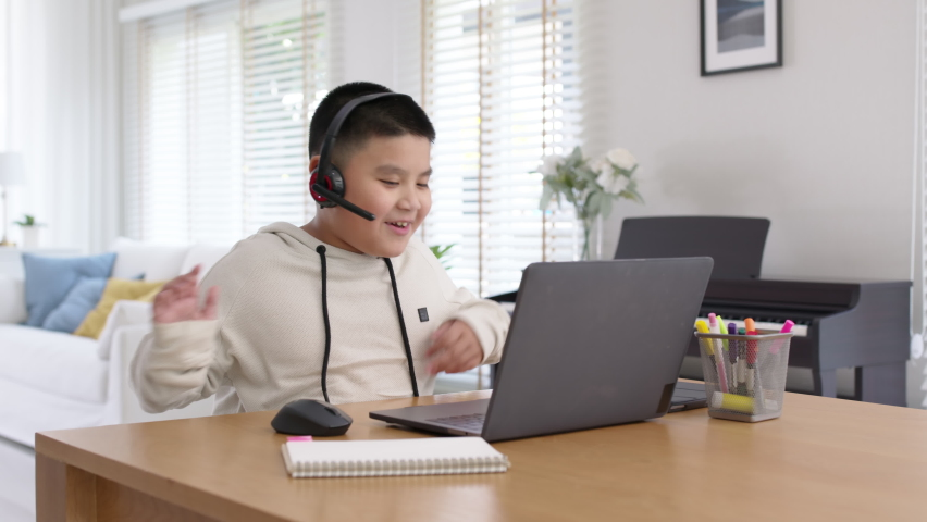 Young asia boy student wear headset headphone with computer laptop videocall talk present online e-learning class study with teacher, social distance learn language at home, homeschooling concept. Royalty-Free Stock Footage #1069270189