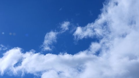 Time-lapse video of beautiful white cumulus clouds moving fast by strong wind in deep blue Mediterranean sky