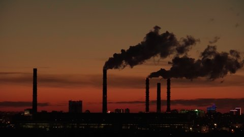 Smoke from industrial chimneys at sunset. Toxic smoke from a thermal power plant in an industrial area. Industrial landscape