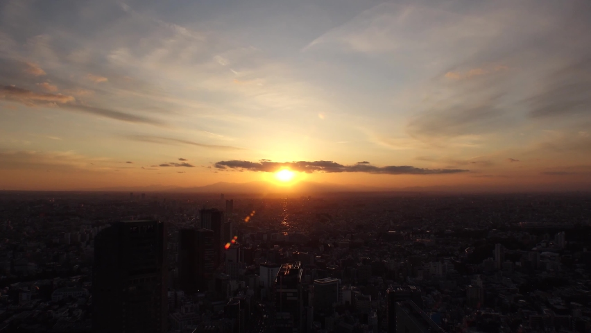 TOKYO, JAPAN : Aerial sunrise CITYSCAPE of TOKYO and MOUNT FUJI. View of rising sun and buildings around Shibuya. Japanese city life and nature concept. Time lapse zoom out video, night to morning.