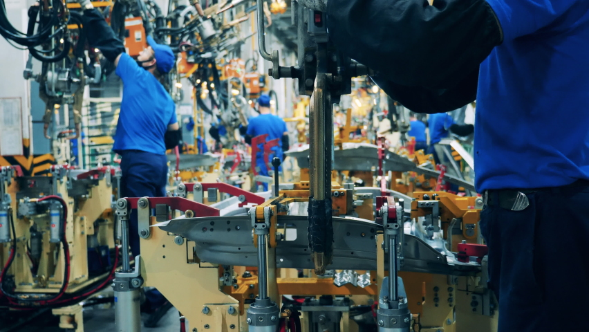 Automobile factory facility, car production process. Car factory worker using a welding machine at a car production factory   Shutterstock HD Video #1069303390