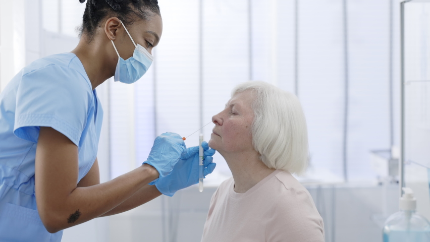 Young female medical worker in protective mask and gloves taking PCR test sample from nose of woman pensioner patient in hospital room . Concept of Covid diagnostic. Royalty-Free Stock Footage #1069304059