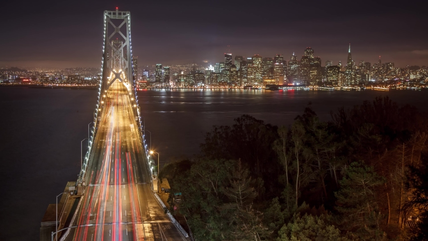 Time Lapse of traffic driving across the Bay Bridge in San Francisco. The buildings of San Francisco can be seen in the distance. Time Lapse.