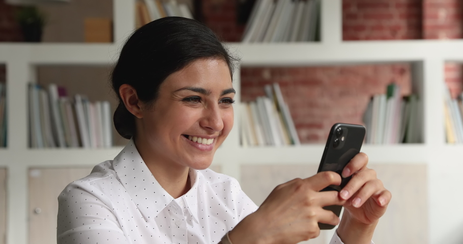Indian woman sit indoor hold smartphone enjoy remote chat in social media network, distant communication. Satisfied user of e-business app, share information across internet. Modern tech usage concept Royalty-Free Stock Footage #1069342516