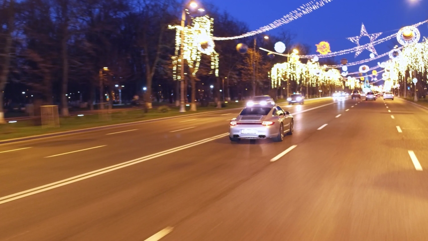 Bucharest,Romania 12.20.2020: Crane rolling shot of a Porsche 911 Carrera 4s luxury sport car driving on a city street with Christmas lights at night during quarantine   Shutterstock HD Video #1069343476