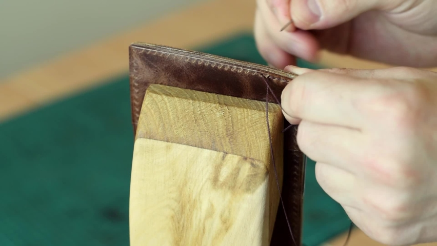 The process of manufacturing a leather cardholder.Artisan sewes the details of a cardholder fixed in a wooden saddler.Handmade leather goods.Hobby concept.Hands close-up, slow motion. Royalty-Free Stock Footage #1069345159