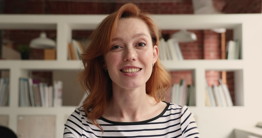 Head shot portrait young redhead woman talk to webcam participate in videoconference negotiate to clients remotely using modern tech and internet connection. Video call event by work or study concept Royalty-Free Stock Footage #1069356016