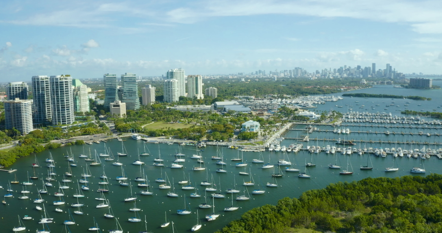Aerial drone view of Coconut Grove harbor full of boats with downtown Miami in the back