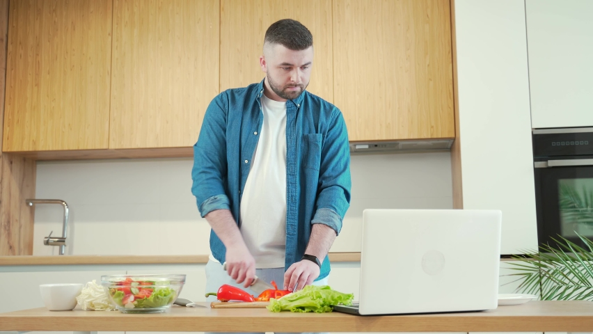 Young handsome bearded man preparing food online at home in the kitchen using laptop. Male cuts vegetables at the table for a vegetarian salad and watches instructional video tutorials cooking recipe