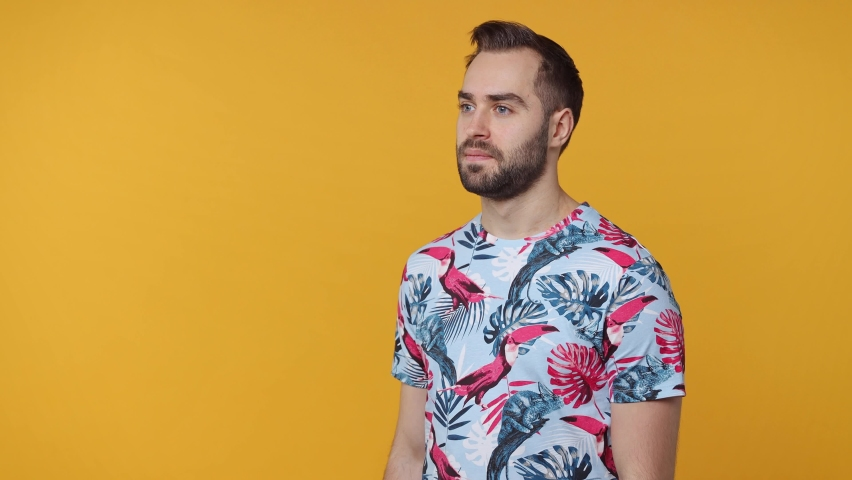 Joyful cheerful shocked bearded young man 20s in summer t-shirt isolated on yellow color background studio. People lifestyle concept. Screaming on megaphone pointing index finger aside clenching fists