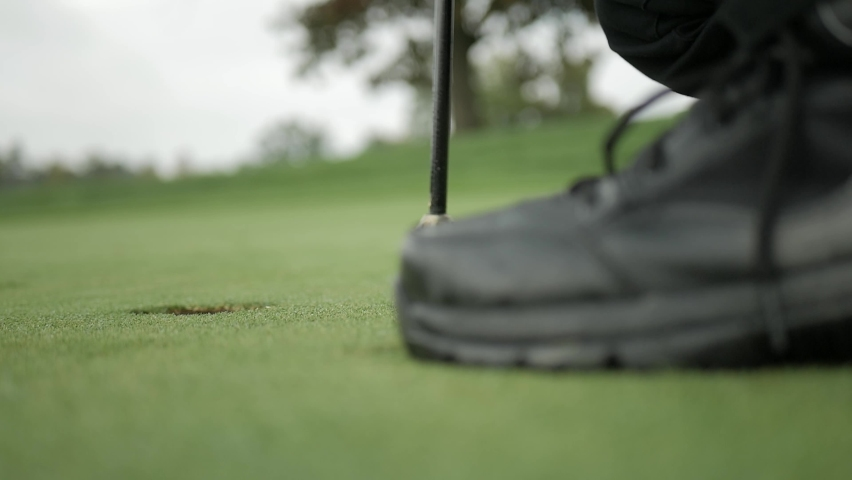 A perfectly focused shot of a golf ball being putt into the hole. | Shutterstock HD Video #1069414357