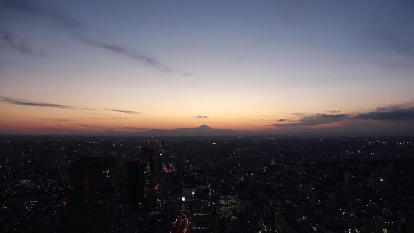 TOKYO, JAPAN : Aerial sunrise CITYSCAPE of TOKYO and MOUNT FUJI. View of rising sun and buildings around Shibuya. Japanese city life and nature concept. Time lapse zoom in video, night to morning.
