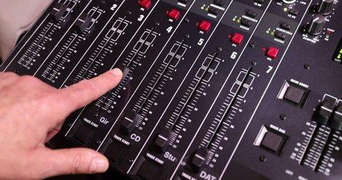 Pan close up on finger on an audio mixer slider