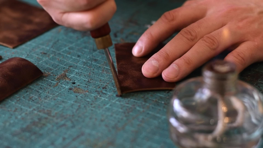 The process of manufacturing a leather cardholder.Processing the edges of leather workpieces with crimping tool.Leather handicrafts.Hobby concept.Artisan's hands close-up, slow motion.  Royalty-Free Stock Footage #1069454968