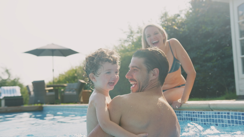 Father with young son playing and having fun on summer vacation in outdoor swimming pool as mother sits on edge - shot in slow motion Royalty-Free Stock Footage #1069462147