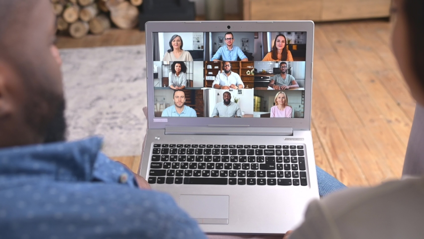 Back view an African-American young couple is using laptop for video meeting with friends, co-workers sitting on the couch at home, the computer screen with many profiles of diverse people on it | Shutterstock HD Video #1069471696