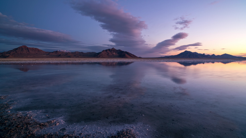 Time lapse of colorful sunrise reflecting over the Great Salt Lake as water covers the Bonneville Salt Flats in Utah.