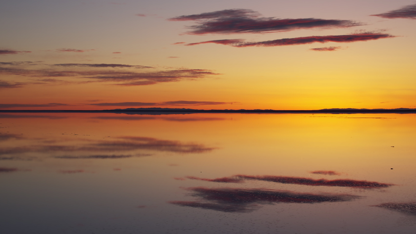 Sunrise reflection over the Great Salt Lake as water shimmers covering the Bonneville Salt Flats in Utah.