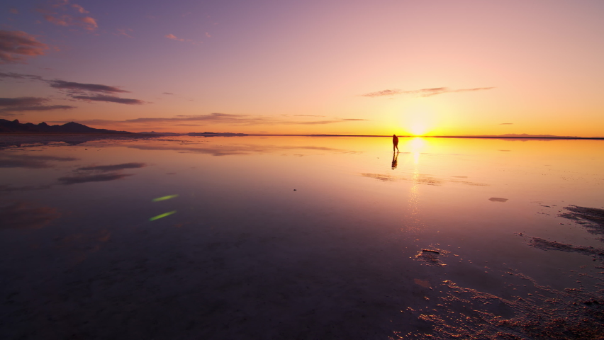 Person standing in water covering the Bonneville Salt Flats during sunrise as colors reflect in the lake.