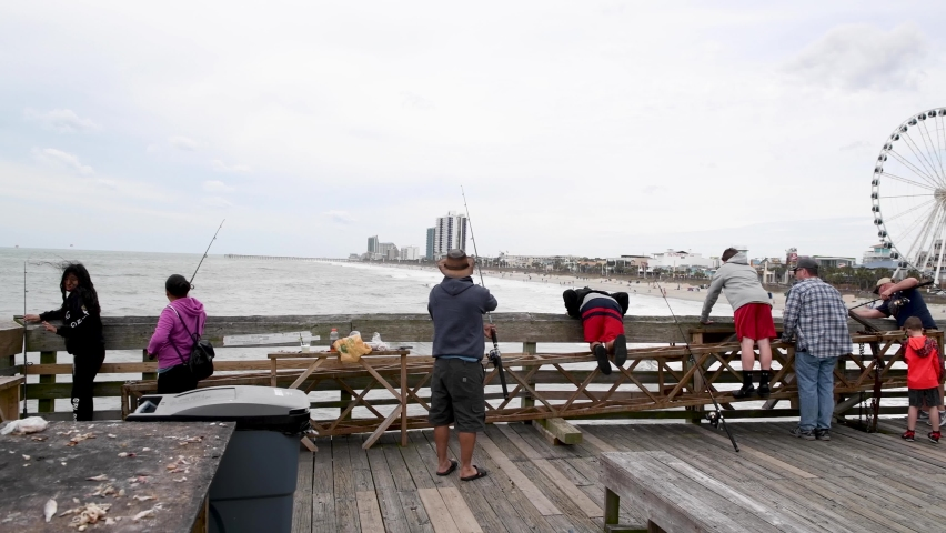 MYRTLE BEACH, SC - APRIL 2018: Buildings and city beach view from the wooden pier. Myrtle Beach attracts 3 million people annually.