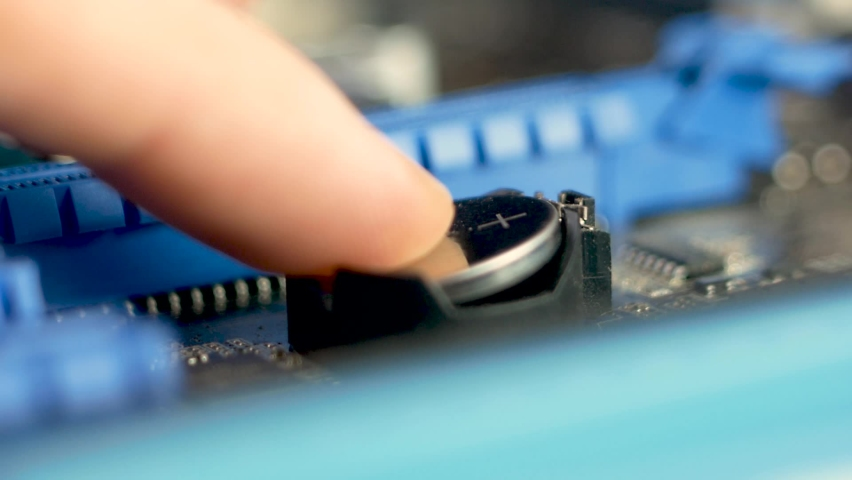 Close up of installing a bios battery on a computer motherboard. Engineering center for the repair of computer components. Computer motherboard chipset repair. Selective focus, shallow depth of field Royalty-Free Stock Footage #1069515430