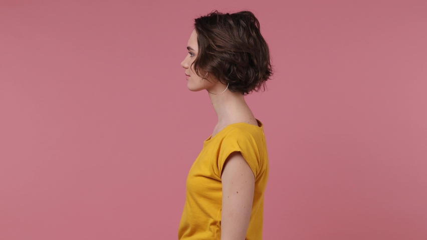 Side profile view surprised short hairdo young woman 20s in basic casual yellow t-shirt turn around camera cover mouth with hand doing winner gesture isolated on pastel pink background studio portrait | Shutterstock HD Video #1069522945