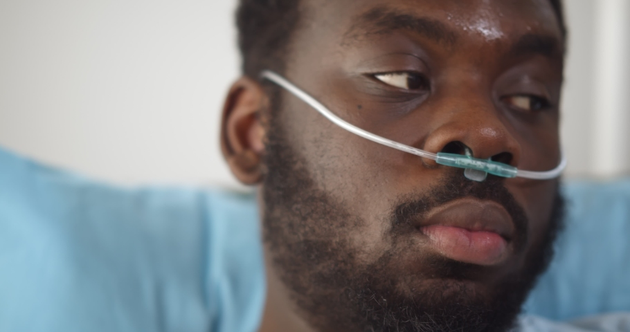 Close up of young african man patient with nasal cannula resting in bed at hospital. Head shot of afro-american sick young man with oxygen tube lying in bed at hospital ward feeling unwell Royalty-Free Stock Footage #1069523053