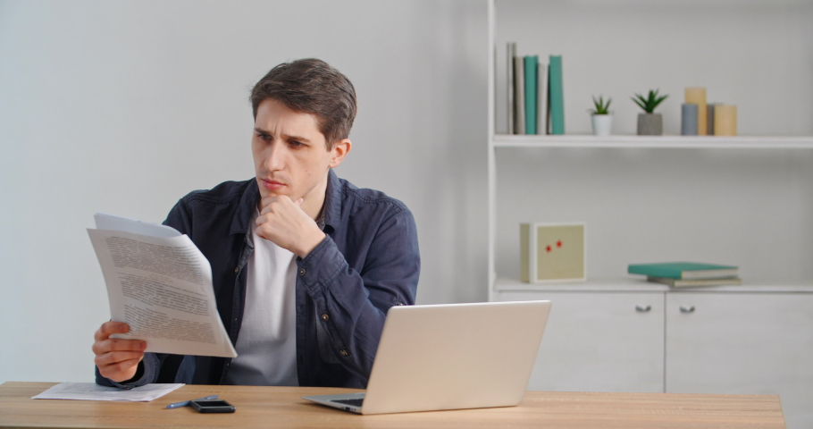 Concentrated caucasian millennial businessman sitting at home desk or in office, looking at documents, reading letter paper, looking in financial statement, receiving notice from bank, doing paperwork Royalty-Free Stock Footage #1069523944