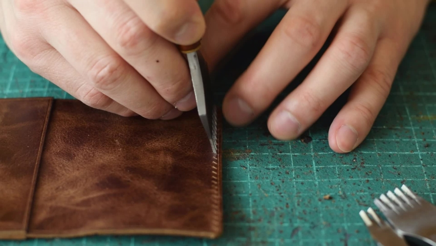 The process of manufacturing a leather cardholder. Punching holes in the work piece with a metal puncher. Handmade leather goods. Hobby concept. Tanner's hands close-up, slow motion. Royalty-Free Stock Footage #1069571008