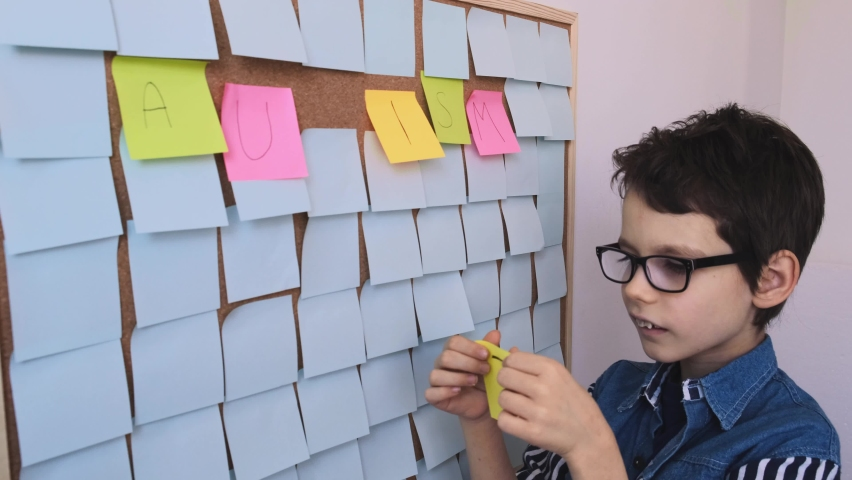 Autistic boy sticks a sticker with the note Autism on a corkboard. Autism awareness concept. Royalty-Free Stock Footage #1069604314