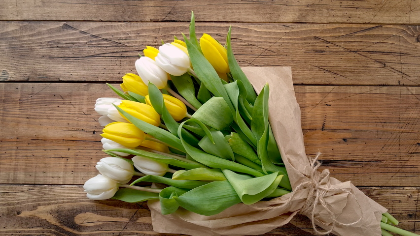 Hands untie a tulips bouquet on a wooden table top view  Royalty-Free Stock Footage #1069607251