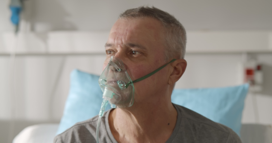 Portrait of elderly person with oxygen mask sitting up in hospital bed and looking around. Sick aged male patient breathing in oxygen mask sitting in bed at hospital ward Royalty-Free Stock Footage #1069624198