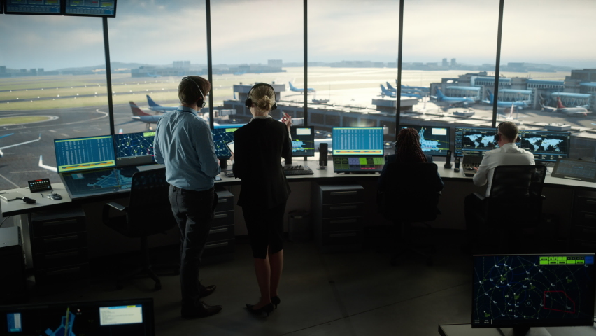 Female and Male Air Traffic Controllers with Headsets Talk in Airport Tower. Office Room is Full of Desktop Computer Displays with Navigation Screens, Airplane Departure and Arrival Data for the Team. | Shutterstock HD Video #1069631443