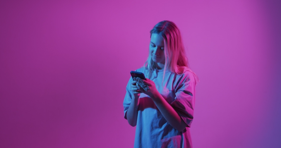 4k video of modern girl with phone. Free creativity. Young blogger typing message. Colored Neon light and background | Shutterstock HD Video #1069698178