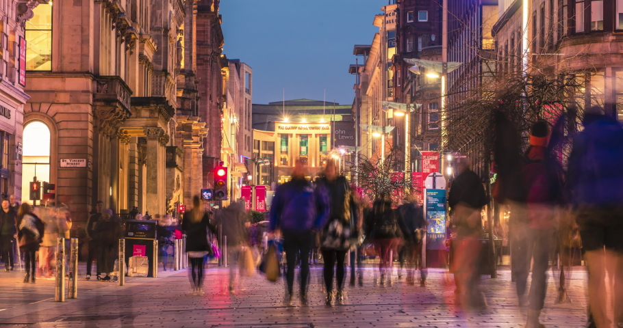 Glasgow, Scotland - February 15, 2019: timelapse of pedestrians walking along the brightly lit Buchanan street in the city centre at night