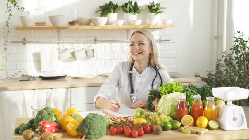 Cute dietitian blogger writes video content about healthy food and healthy eating on her smartphone in her kitchen Royalty-Free Stock Footage #1069713541