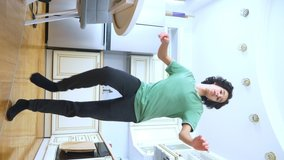 vertical video. handsome curly guy dancer cheerfully dancing at home in the kitchen .