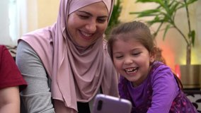 Ramadan Celebrations Online. Happy traditional Muslim family, mother in hijab and children together at home using smartphone to call friends during quarantine. Eid mubarak