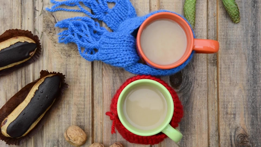 Two cups of coffee with scarves and chocolate dessert circular motion camera
